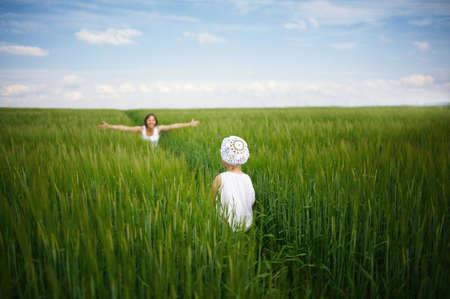 緑のスプリング フィールドで彼女の赤ん坊を会議の母 写真素材