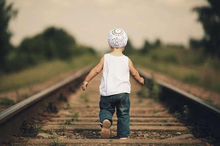 kleine mooie meisje speelt op spoorlijn Stockfoto