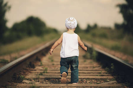 little beautiful girl plays on railroad