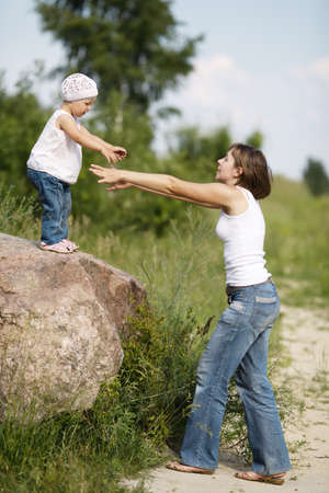 mom helps daughter to go to the ground from large stone photo