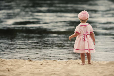 little girl standing with her back on the coast of river photo
