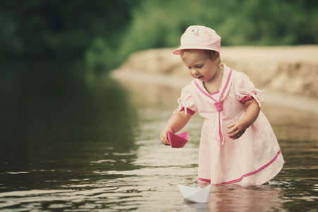 paper boat: little girl plays with paper boats in river