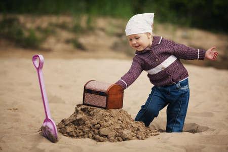 gold shovel: little funny girl hunting for treasure Stock Photo
