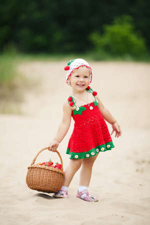 little happy girl with basket full of strawberries