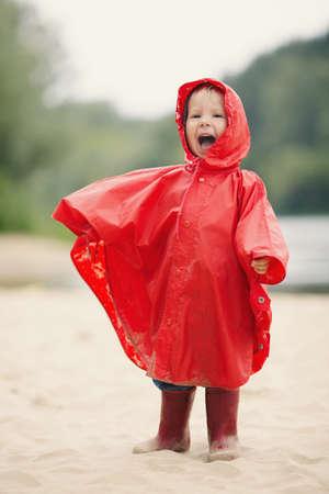 lloviendo: Niña divertida con el impermeable