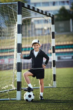 Little boy plays football on stadium photo