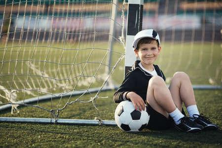 Jongetje speelt voetbal op stadion Stockfoto