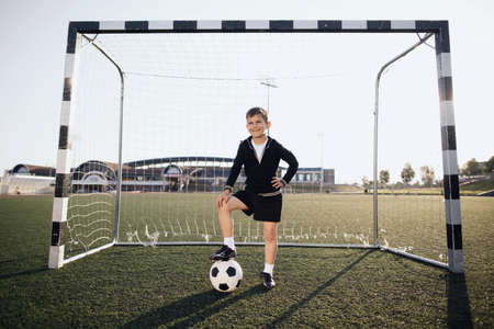 Little boy plays football on stadium photo
