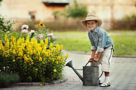 cute little boy watering flowers watering can Stock Photo