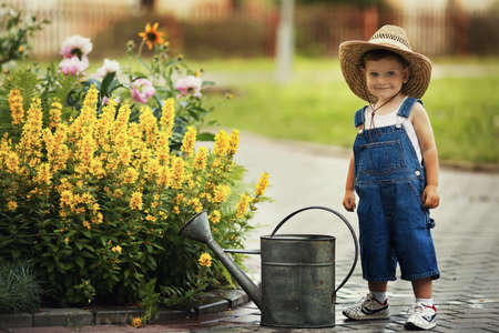 cute little boy watering flowers watering can Banque d'images