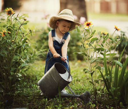 home garden: cute little boy watering flowers watering can Stock Photo