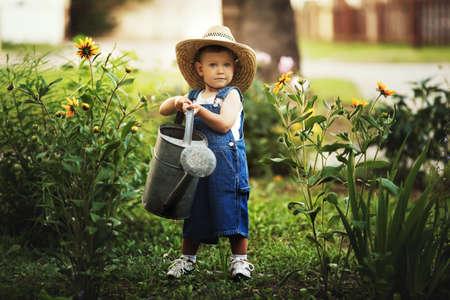 cute little boy watering flowers watering can Standard-Bild