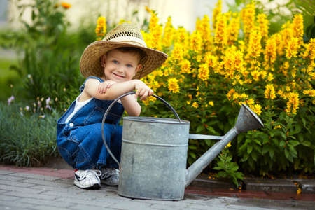 cute little boy watering flowers watering can Standard-Bild