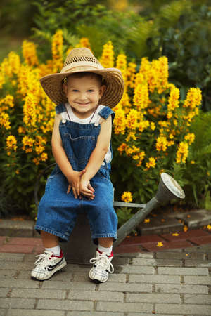 cute little boy watering flowers watering can Stockfoto