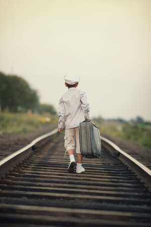 walk away: little boy with suitcase on railroad