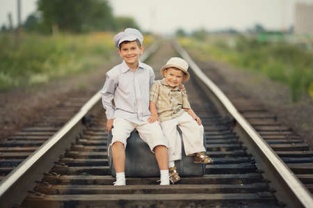 Two happy boys with suitcase on railways photo