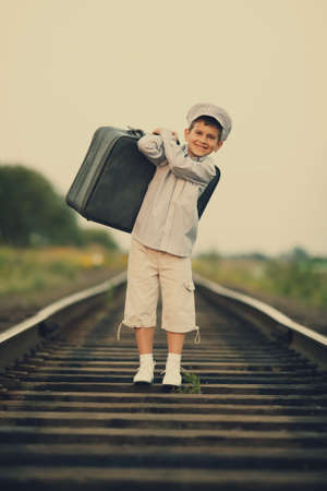 little boy with suitcase on railroad photo