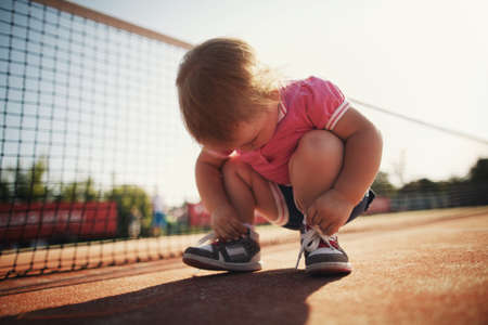 little girl learning to tie shoelaces photo