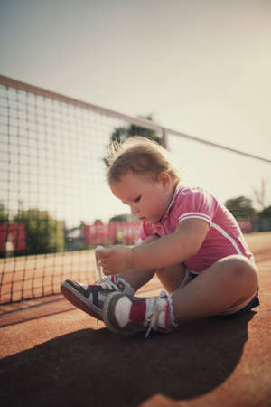 teen girls feet: little girl learning to tie shoelaces