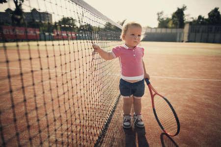 kleine lustige Mädchen mit Tennisschläger