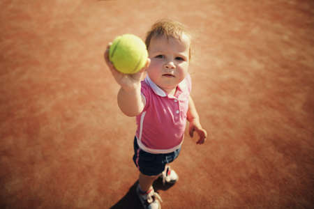 little funny girl with tennis ball photo