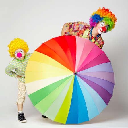 lustige Clown mit bunten Regenschirm auf weißem