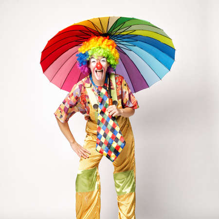 funny clown with colorful umbrella on white photo