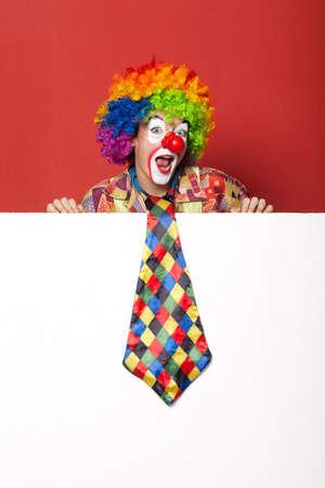 lustige Clown mit Krawatte auf leere weiße Tafel