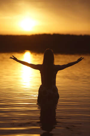 beautiful girl in water on sunset silhouette photo