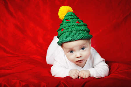 little cute baby with christmas tree hat on red background Stock Photo - 22789637