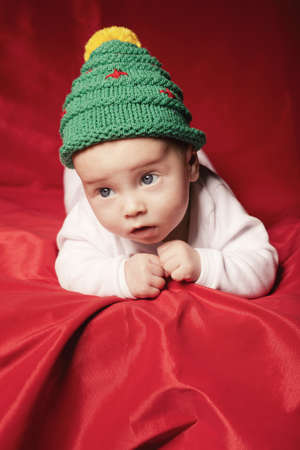 little cute baby with christmas tree hat on red background Stock Photo - 22789641