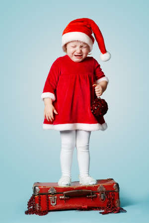 little crying girl standing on red suitcase with gifts photo