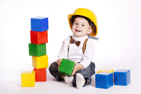 little engineer with protective helmet plays with cubes Stockfoto
