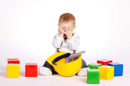 little engineer with protective helmet plays with cubes photo