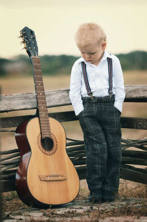 country music: cute little boy with guitar on location