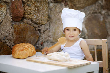 cute little boy with chef hat cooking photo