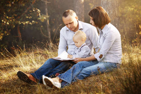 Happy family reading book in park photo