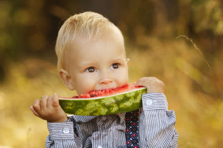 cute little boy eats watermelon photo