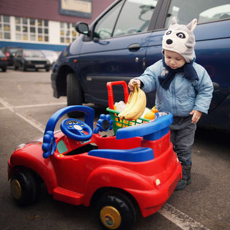 boy on parking with shopping carriage photo