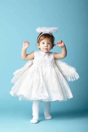Beautiful little angel on blue background photo