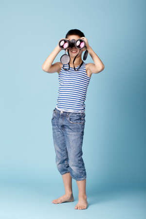 little sailor with binoculars on sky blue background photo