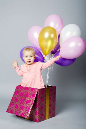 cute little girl sitting on gift box with balloons photo