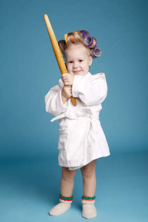 young housewife with rolling pin on blue wall photo