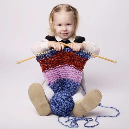 cute little girl knitting scarf photo