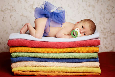 cute newborn baby lying on colorful towels photo