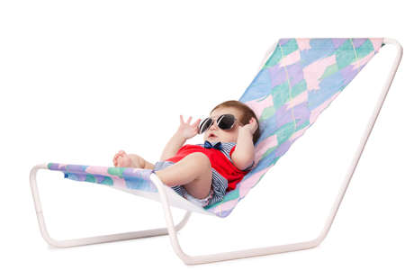 cute baby lying on lounger isolated on white photo