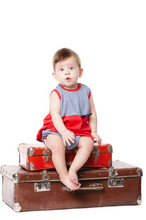beautiful baby with suitcase isolated on white photo