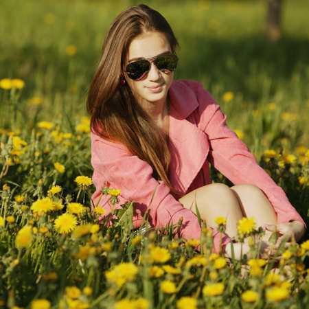 beautiful young girl with sunglasses in dandelion field photo
