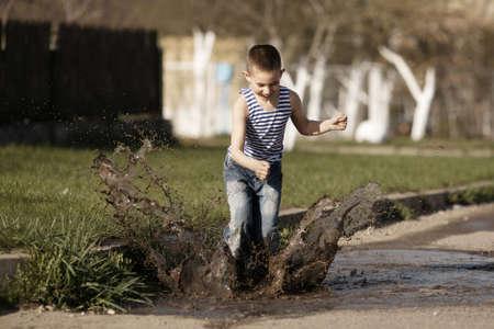 little happy boy jumping in puddle Standard-Bild