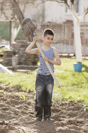 little happy boy working with shovel in garden photo